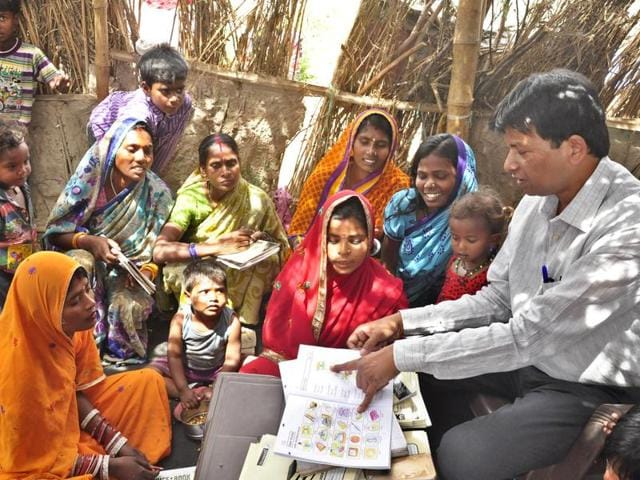 Advocate Hariom Jindal teaching slum women and their children at a shanty on Hambran Road in Ludhiana on Friday.