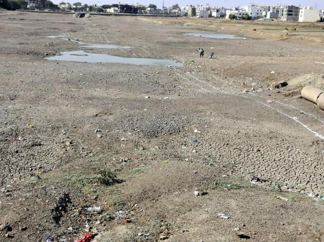 Commuters ride a bike on the bed of dried up Pipliyahana Lake on Eastern Ring Road in Indore.