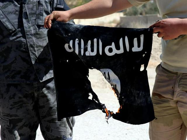 Iraqi soldiers hold a flag that they seized from the Islamic State group.