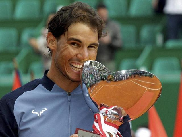Spain's Rafael Nadal holds his cup after defeating France's Gael Monfils.