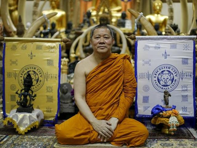 Buddhist monk Phra Prommangkalachan poses for a portrait next to holy cloths with Leicester City's logo.