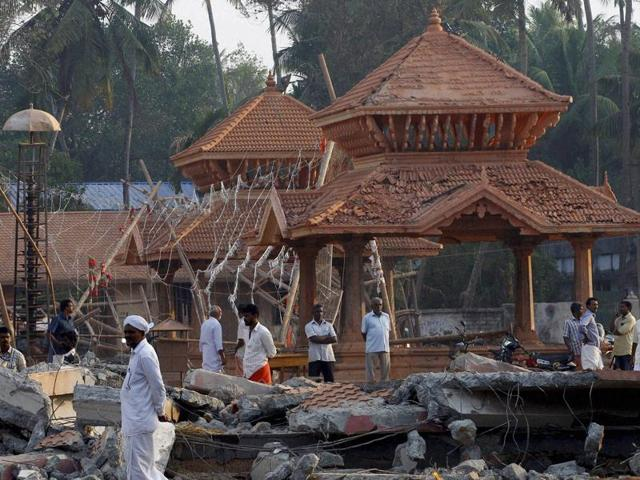People take stock of the damaged structure of the Puttingal Devi temple after the fire accident that claimed more than 100 lives.