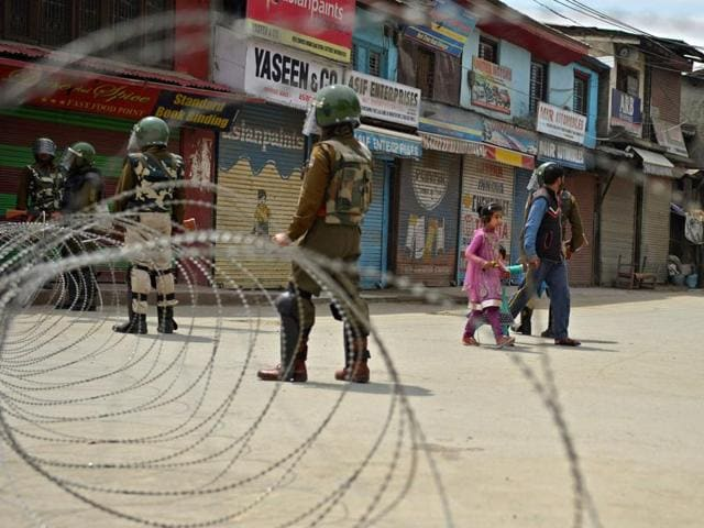 Paramilitary troopers look on as a family walk along a deserted street during a curfew in the Maisuma Area of Srinagar.