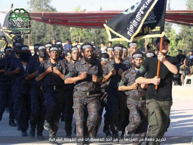 "This file photo shows fighters from Ahrar al-Sham march in the eastern Damascus suburb of Ghouta, Syria.  Syrian rebel groups included factions fighting under the banner of the Free Syrian Army and Ahrar al-Sham announced a new ""battle"" against government forces."