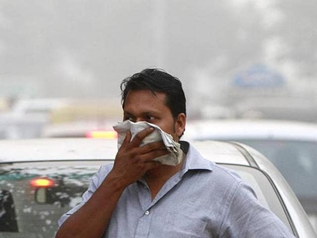 A man covers his face on a smoggy day, at Connaught Place in New Delhi.