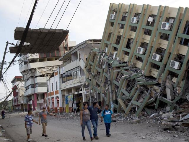 Residents walk past a row of collapsed buildings felled by the 7.8-magnitude earthquake, in Portoviejo, Ecuador. The April 16 quake left a trail of ruin along Ecuador's normally placid Pacific Ocean coast.