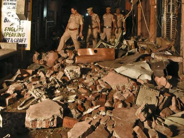 Policemen inspect the site of a fire accident in Delhi's Kailash Nagar.