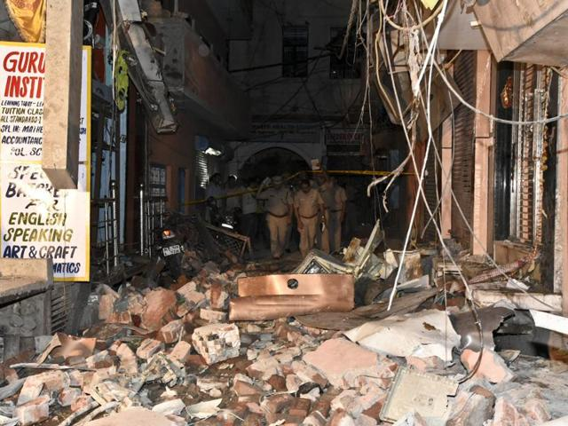 Police personnel inspect street number 17 of Gandhinagar in East Delhi, where a LPG cylinder exploded, on Monday evening.