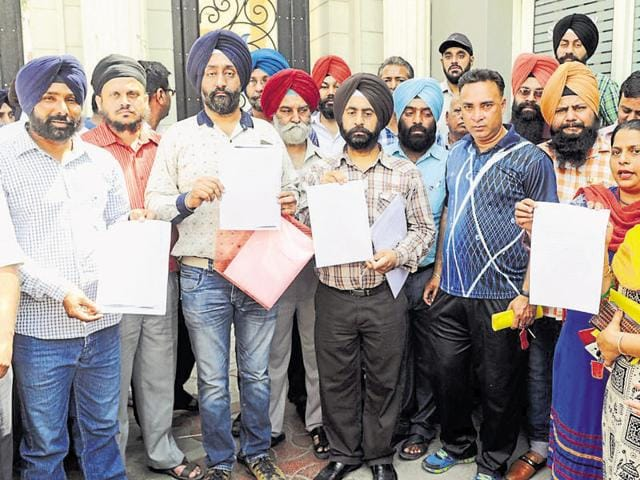 Parents showing the high court's order while protesting outside Budha Dal Public School in Patiala on Monday.
