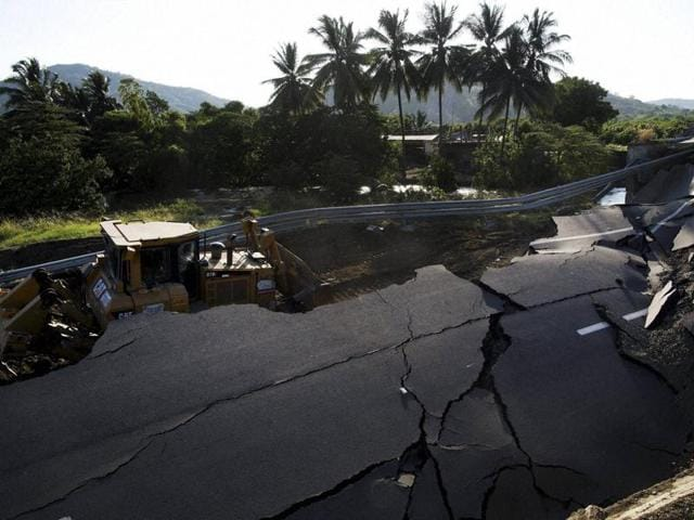 A bulldozer works to clear a section of highway that collapsed due to the 7.8-magnitude earthquake that struck Ecuador on April 16.