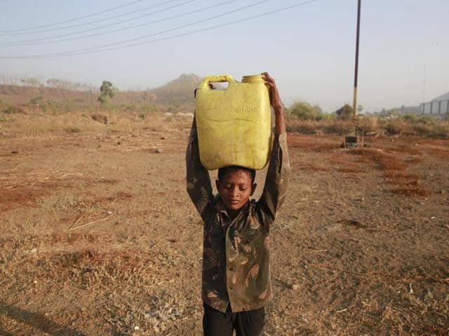 A boy who migrated from drought-hit areas of Maharashtra carries water to his family's makeshift hut in Kukse Borivali.