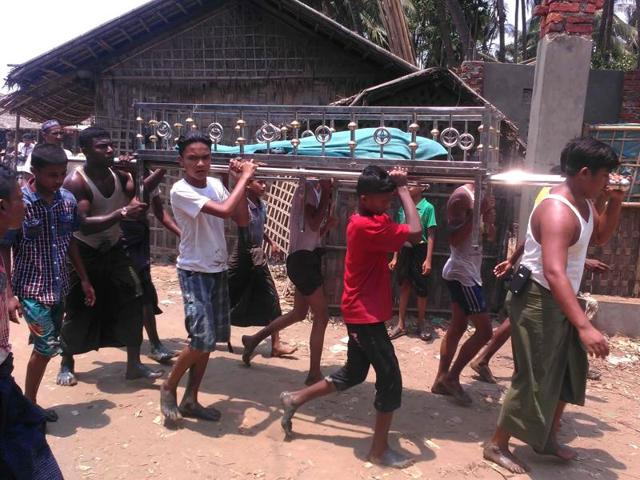 A handout photo taken on April 19, 2016 and released to AFP from anonymous Rohingya Muslim minority residents shows people carrying a dead body after a boat capsized off the coast in Sittwe.