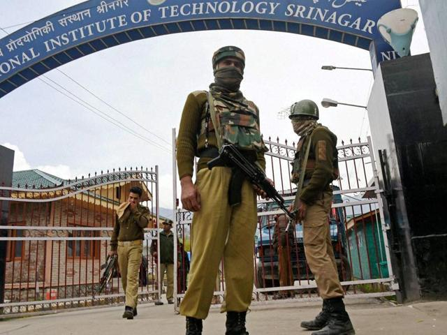 Police and CRPF stand guard outside the NIT Srinagar campus following tension between local and non-Kashmiri students.
