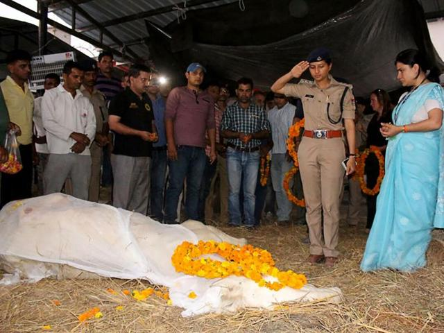 A police officer salutes the body of police horse Shaktiman during a ceremony in Dehradun on April 21, 2016