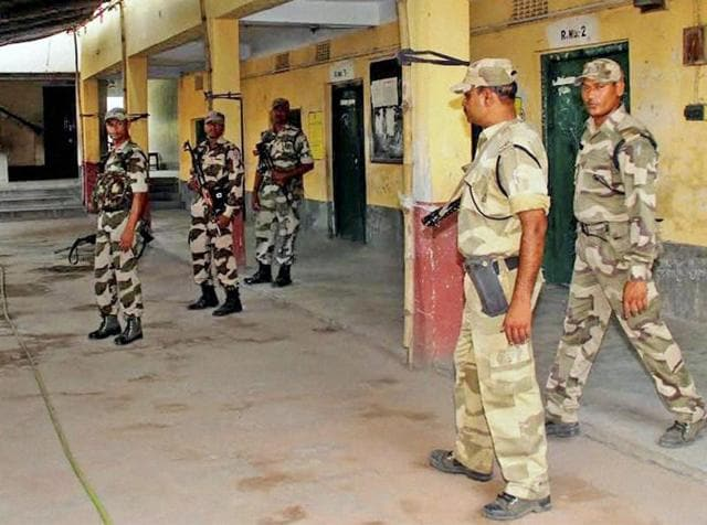 Central paramilitary personnel stand guard outside a polling booth on the eve of the third phase of polling in Burdwan on Wednesday.