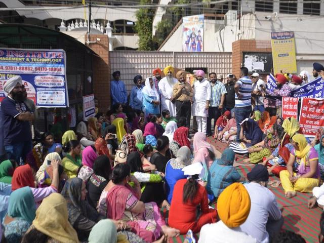 District education officer Satinder Bir Singh (centre) addressing parents protesting against the re-admission fee and the high fee structures in private schools outside Sri Guru Harkrishan Public School in Amritsar on Thursday.