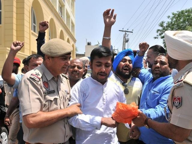 Police detaining AAP workers protesting outside enforcement directorate in Jalandhar on Friday.
