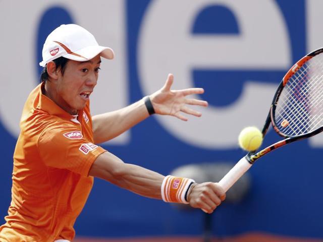 Kei Nishikori returns the ball to Alexandr Dolgopolov  during the Barcelona open tennis tournament.