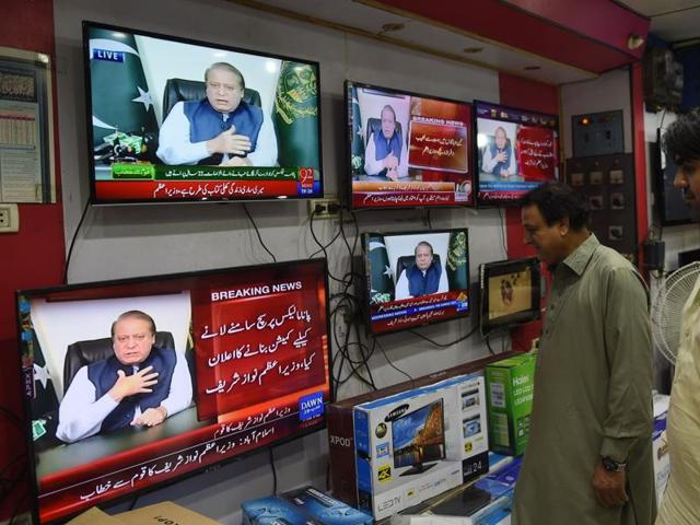 Pakistani men watch a televised addresses to the nation by Prime Minister Nawaz Sharif in Karachi on April 22, 2016.