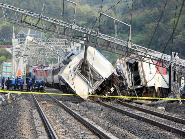 South Korea railway workers struggle to put a derailed passenger train back on track in the southern port city of Yeosu.