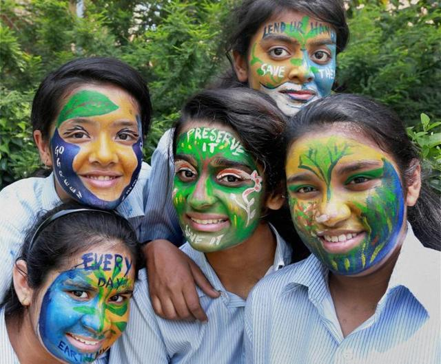 Students paint their faces with awareness messages on World Earth Day in Gurgaon on Friday.
