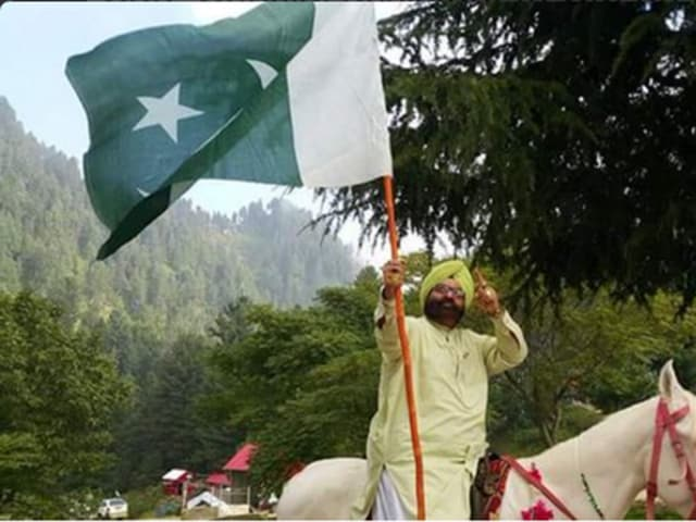 In this photo, minority affairs minister of Khyber-Pakhtunkhwa province Sardar Soran Singh poses with a Pakistani flag.