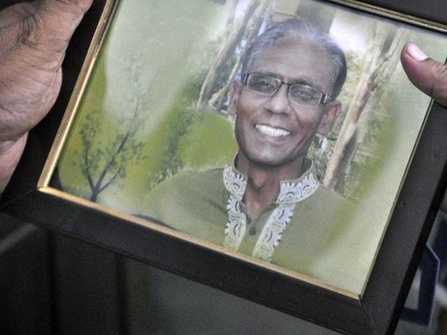 A man holds a portrait of Bangladeshi professor Rezaul Karim Siddique, who was hacked to death in Rajshahi.