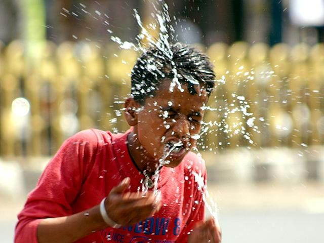 A boy washing his face with chilled water for relief from scorching heat.