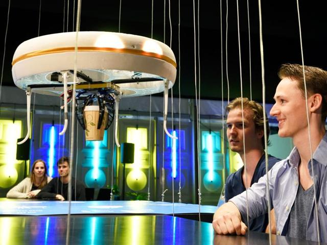 A flying drone bringing drinks to customers in the world's first drone cafe in Eindhoven.
