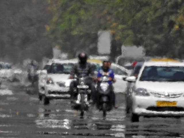 Vehicles driving along a road are seen through heat haze in Chandigarh.