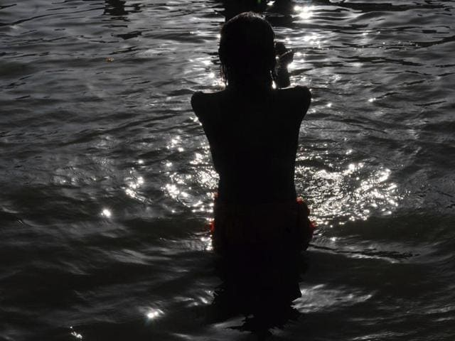 A Naga sadhu offers prayers after taking a holy dip in the Shipra river in Ujjain.