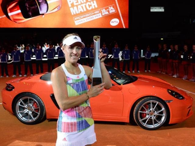 Porsche Tennis Grand Prix winner Angelique Kerber of Germany poses with her trophy in her reward, a Porsche Boxster 718, after winning the final against Laura Siegemund of Germany.