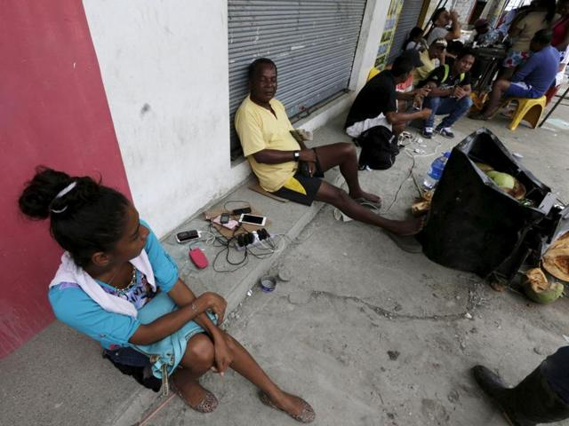 Residents charge their mobile phones on a sidewalk in Pedernales in quake-hit Ecuador.