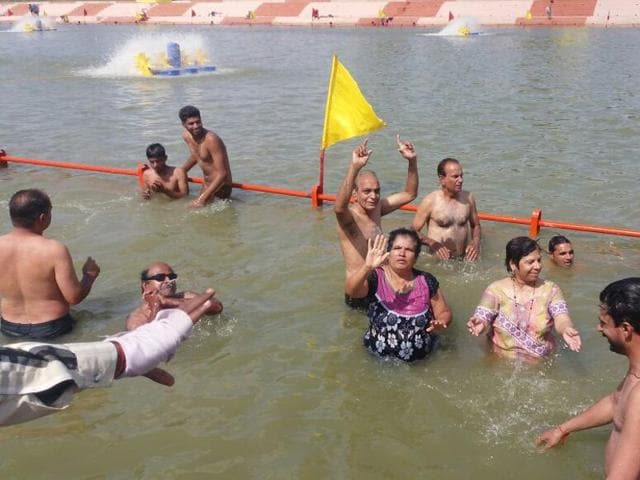 Differently abled people take holy dip in Kshipra in Ujjain on Sunday.
