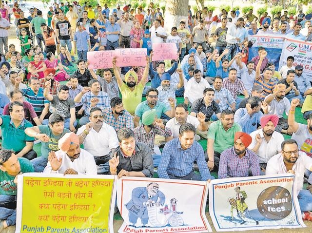 Holding posters, parents raising slogans against private schools and the district administration in Amritsar on Sunday.
