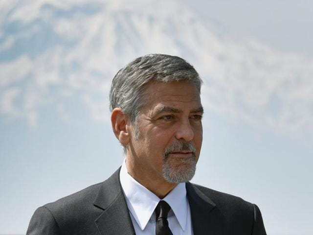 US actor George Clooney poses with Ararat mountain in background, as he attends a ceremony at the Armenian Genocide Memorial in Yerevan on April 24, 2016.
