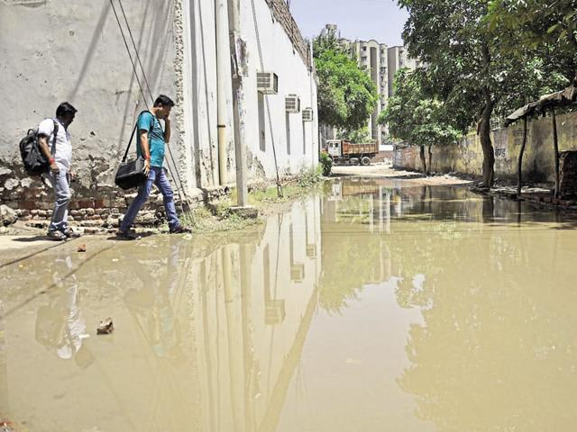 Water overflowing from a sewer inundates a road in the sector.