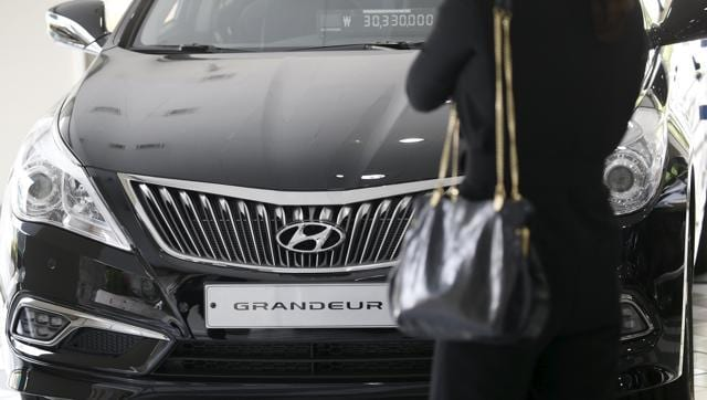 A visitor looks at a Hyundai Motor's Grandeur sedan at its dealership in Seoul, South Korea.  Hyundai is looking to shed its mass-market image in India and go premium.