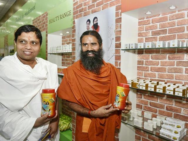 """Baba Ramdev and Acharya Balkrishna shows their """"Patanjali"""" products before addressing a Press Conference in New Delhi. (Photo by Arvind Ashok Nigam/ Hindustan Times)"""