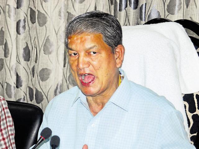 File photo of former Uttarakhand chief minister Harish Rawat (R) addressing a press conference in Dehradun.