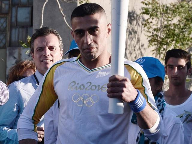 Syrian refugee and amputee swimmer Ibrahim al-Hussein, 27, holds the Olympic Flame torch.