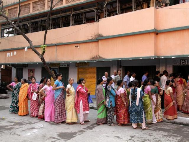 Voters stand in a queue to cast their votes at a polling booth during fourth phase of the West Bengal Assembly elections in Howrah.