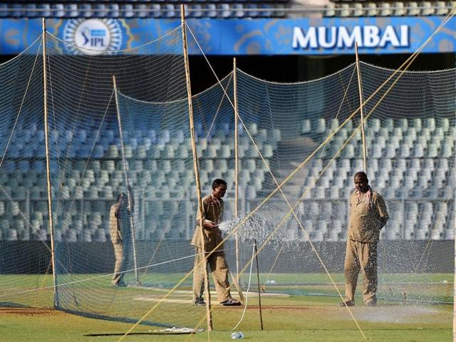 Groundsmen water the pitch at the Wankhede stadium ahead of IPL matches in Mumbai.