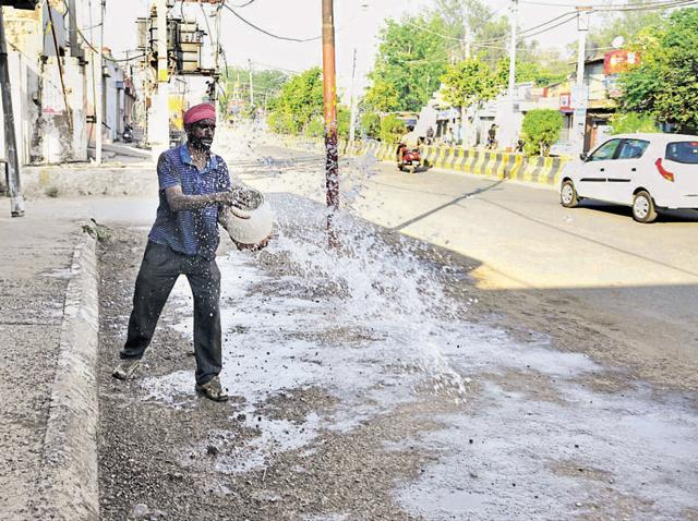 A man sprinkling water on the road in Jalandhar on Tuesday.