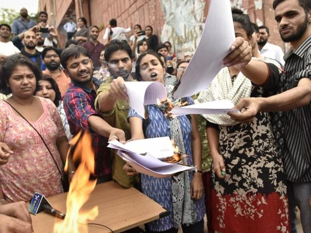 Student leaders  Kanhaiya Kumar, Umar Khalid, Anirban Bhattacharya and Shehla Rashid Shora, among others, burn copies of a report of the panel that looked into the February 9 gathering at JNU where 'anti-India' slogans were allegedly shouted.