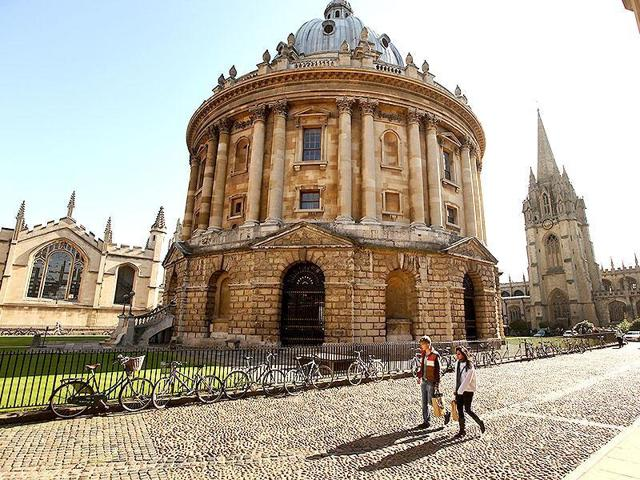 Students walk past the Radcliffe Camera building in Oxford city centre at Oxford University, in Oxford, England.