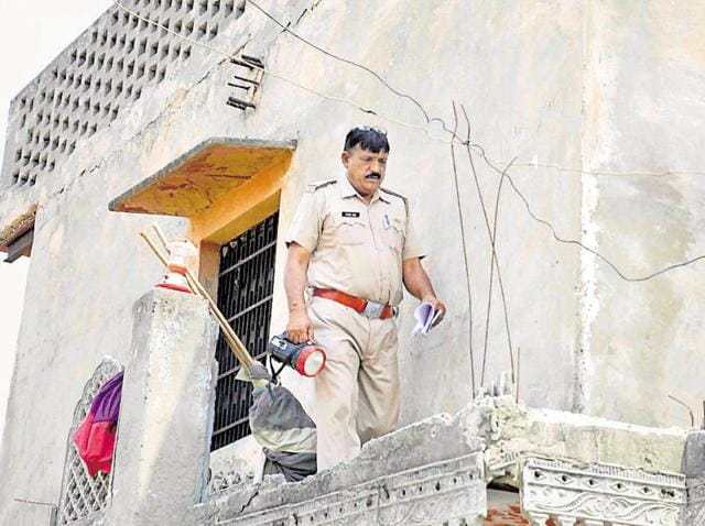Police at the crime scene where the robbers gang-raped the elder daughter, aged 19 years, and molested her 16-year-old sister.