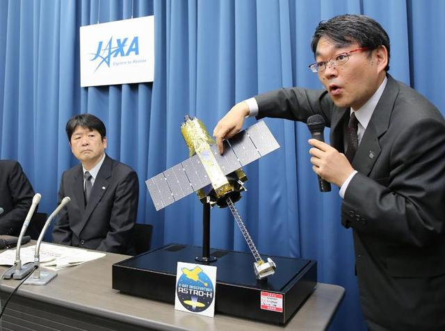 Takashi Kubota (R), space program director of the Japan Aerospace Exploration Agency (JAXA), answers questions beside a miniature version of the ultra high-tech satellite