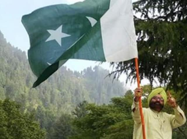 In this photo, Sardar Soran Singh poses with a Pakistani flag.