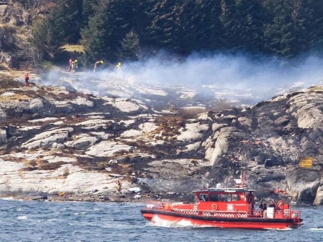 A search and rescue vessel patrols off the island of Turoey, Norway, as emergency workers attend the scene of a helicopter crash believed to have 13 people aboard.